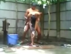 Indian Piece of baggage Bathing outside nude and dissimulating a street boy